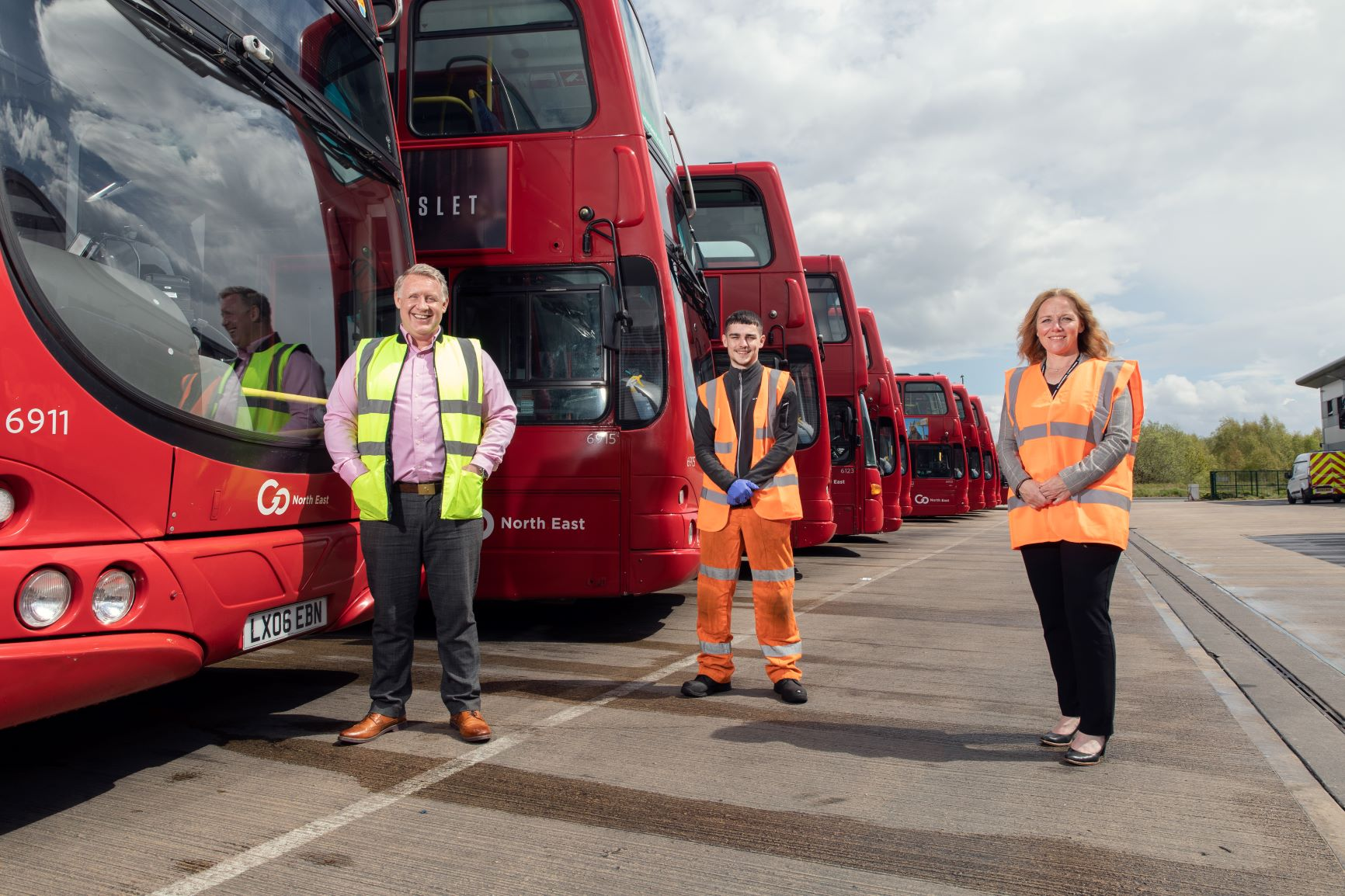 To left of image, red double-decker busses in a line. In foreground three people equally spaced out. On the left is Colin Barnes in a yellow high-vis waistcoat, in the middle is apprentice Oliver Barry in full body orange high-vis and on the right is Suzanne Slater in an orange high-vis vest