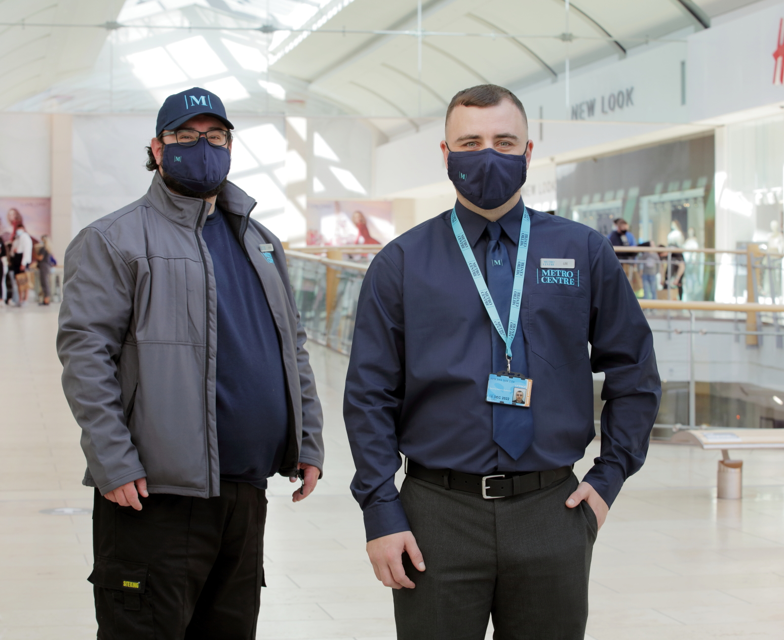 Two Metrocentre staff, both wearing masks. One is wearing a dark blue shirt with a lanyard around their neck with one hand in their suit trouser pocket. The other is wearing a cap and grey jacket