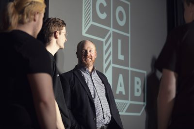 Man with beard in checked shirt and blazer in front of screen with CoLab written within geometric shape. Man is surrounded by other people