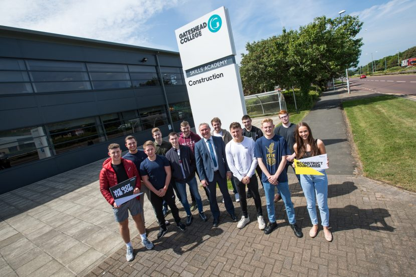 Group of young people stood in semi circle in front of Gateshead College sign with building on the left and trees on the right in the background