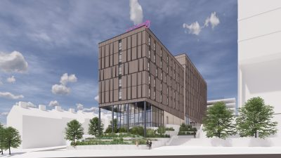 CGI image of Moxy Hotel. Brown large oblong block with slim glass windows throughout. Entrance at the bottom is full glass panels.