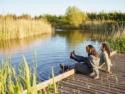 Two women sat on a jetty surrounded by water and grass reeds