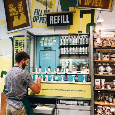 Product refill station in Body Shop store. Man to the left is filling up a bottle at the station. Surrounded by bold and eyecatching green and blue signage. Lines of aluminium bottles are at the top of the station.