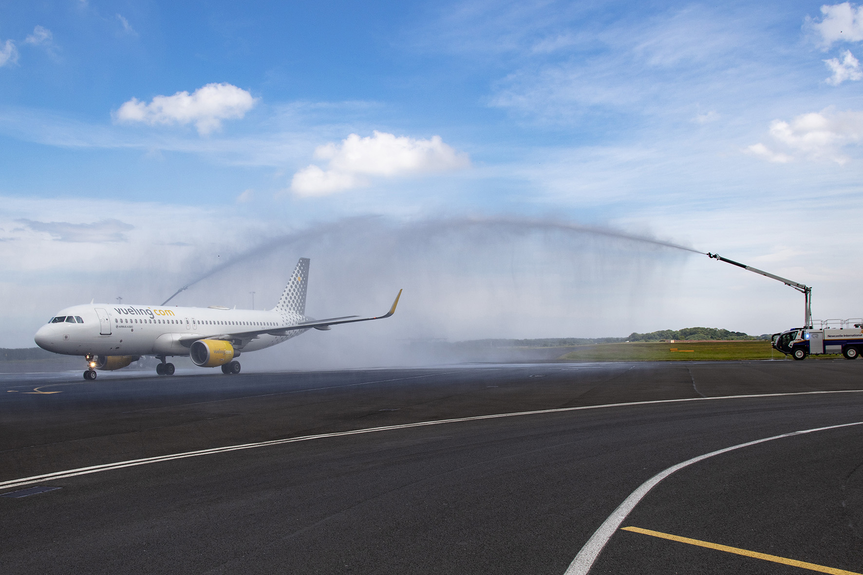 Airplane on runway with large water sprinklers on either side showering the plane as it comes in