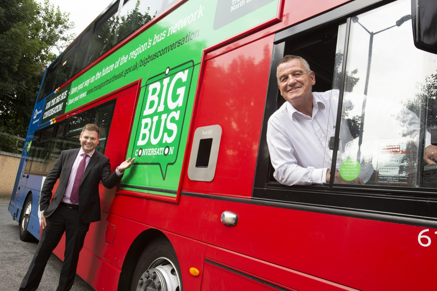 Man dressed in dark suit and purple tie stands beside red double decker bus gesturing towards advert on bus for the Big Bus Conversation. Another man sits in the drivers seat of the bus in a white shirt. Both are smiling towards the camera.