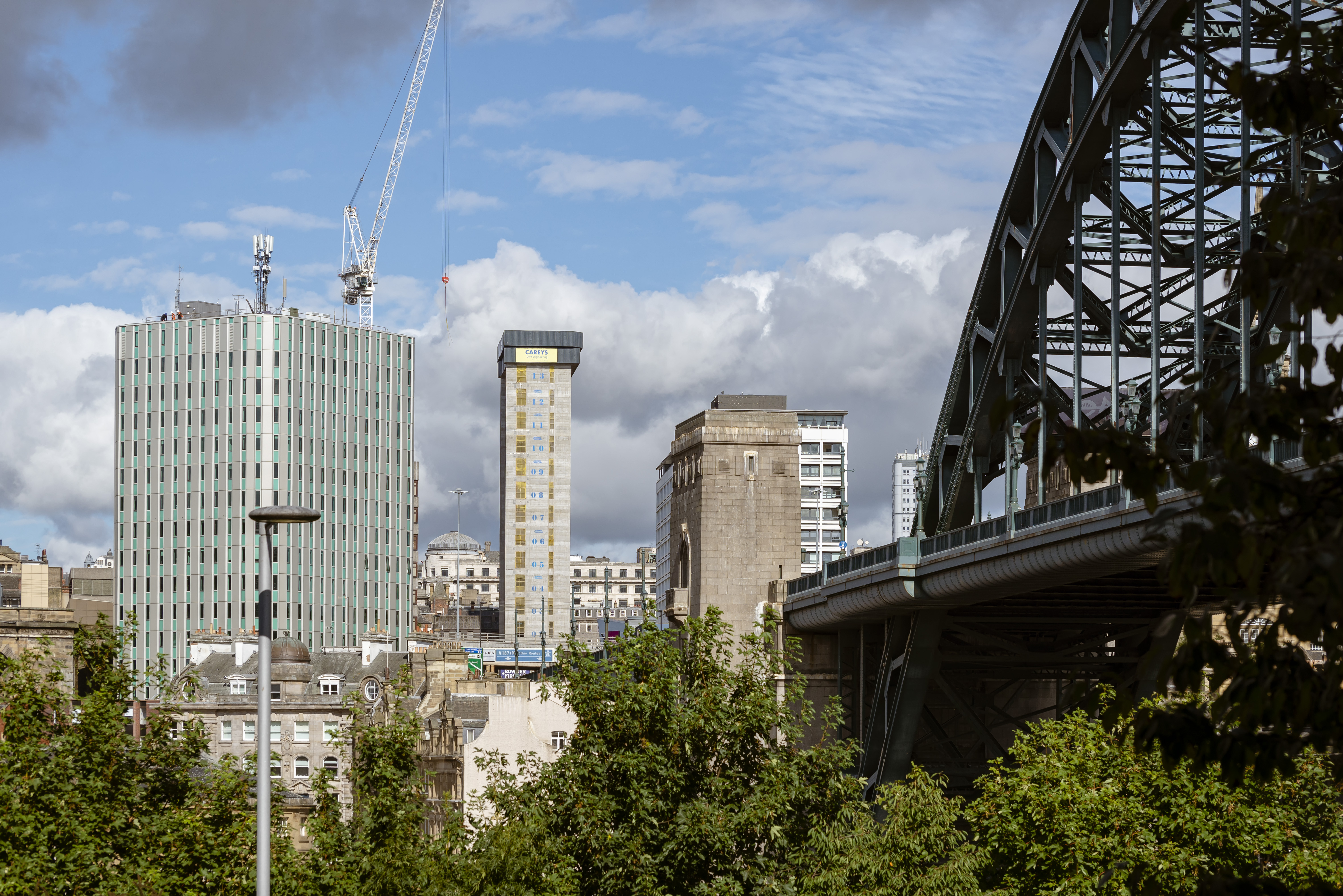Skyline image of Newcastle city centre. The green Tyne bridge is nestled to the right of the image and the new grey concrete of the Bank House building stands tall in the middle of the image with a large crane towering over it to its left. There are green tree tops in the foreground of the image.