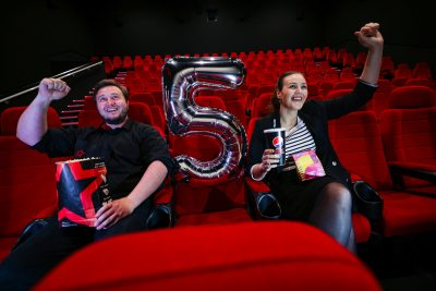 Man and woman sit in a movie theatre on red velvet seats. On the left sits the man with short brown hair and beard in all black clothing. He holds a bag of popcorn and has one fist up in the air in a joyful pose. On the right sits a woman with dark hair slicked back in a ponytail wearing a striped top and black blazer holding a drink in one hand and with fist up in the air like the man. Both are smiling and there is a '5' balloon placed in between them.