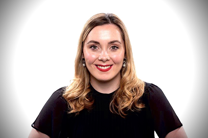 Headshot of Kirsty Russell smiling towards camera head on. Kirsty has shoulder length dark blonde hair, red lips and a short sleeve black top on.