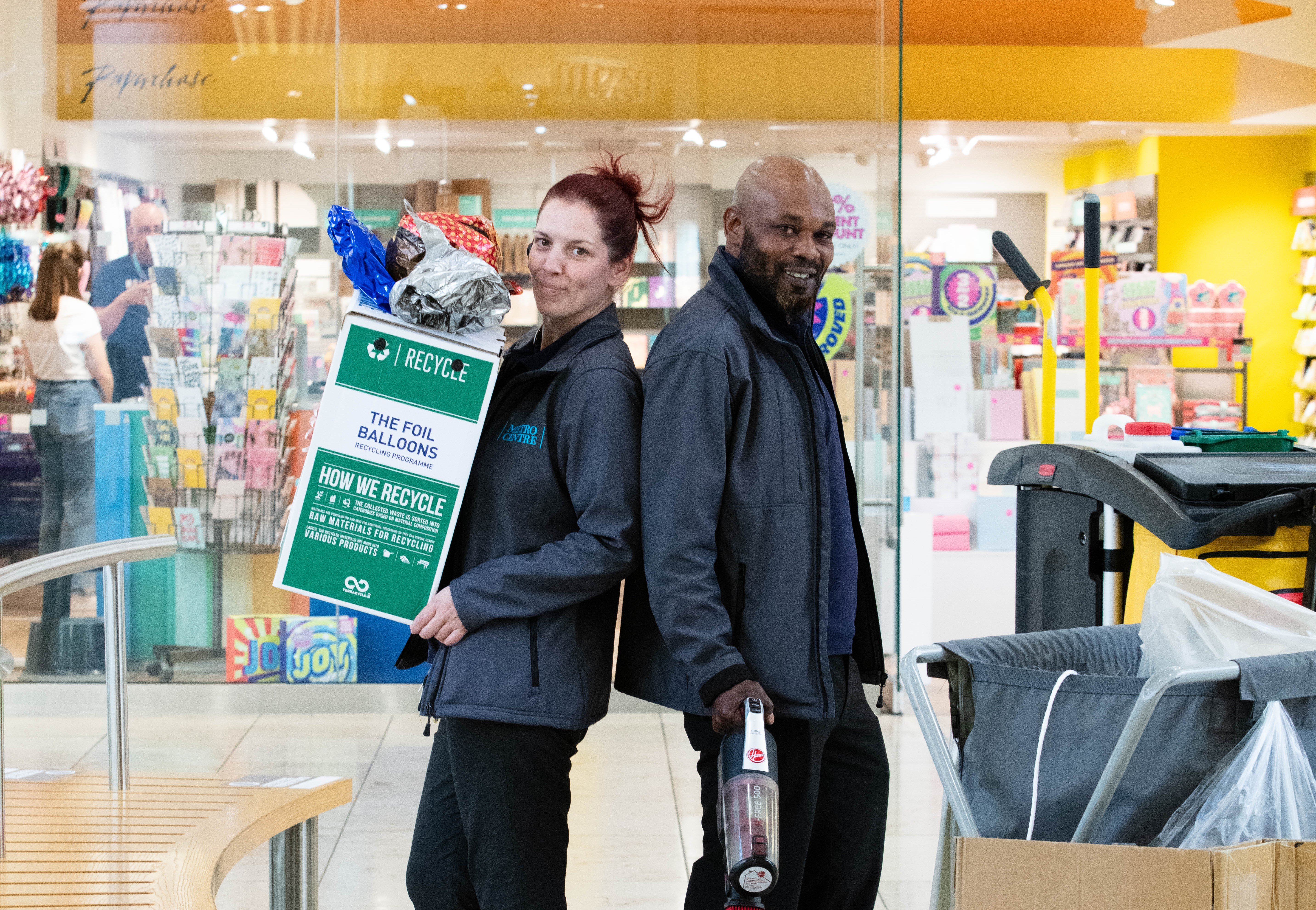 Man and woman stand back to back in centre of image. Woman on the left has red hair tied up in a bun and is holding a cardboard recycling box. Man beside her is bald and has a short beard. He is holding a vacuum cleaner. Both are wearing grey 'Metrocentre' branded fleeces.