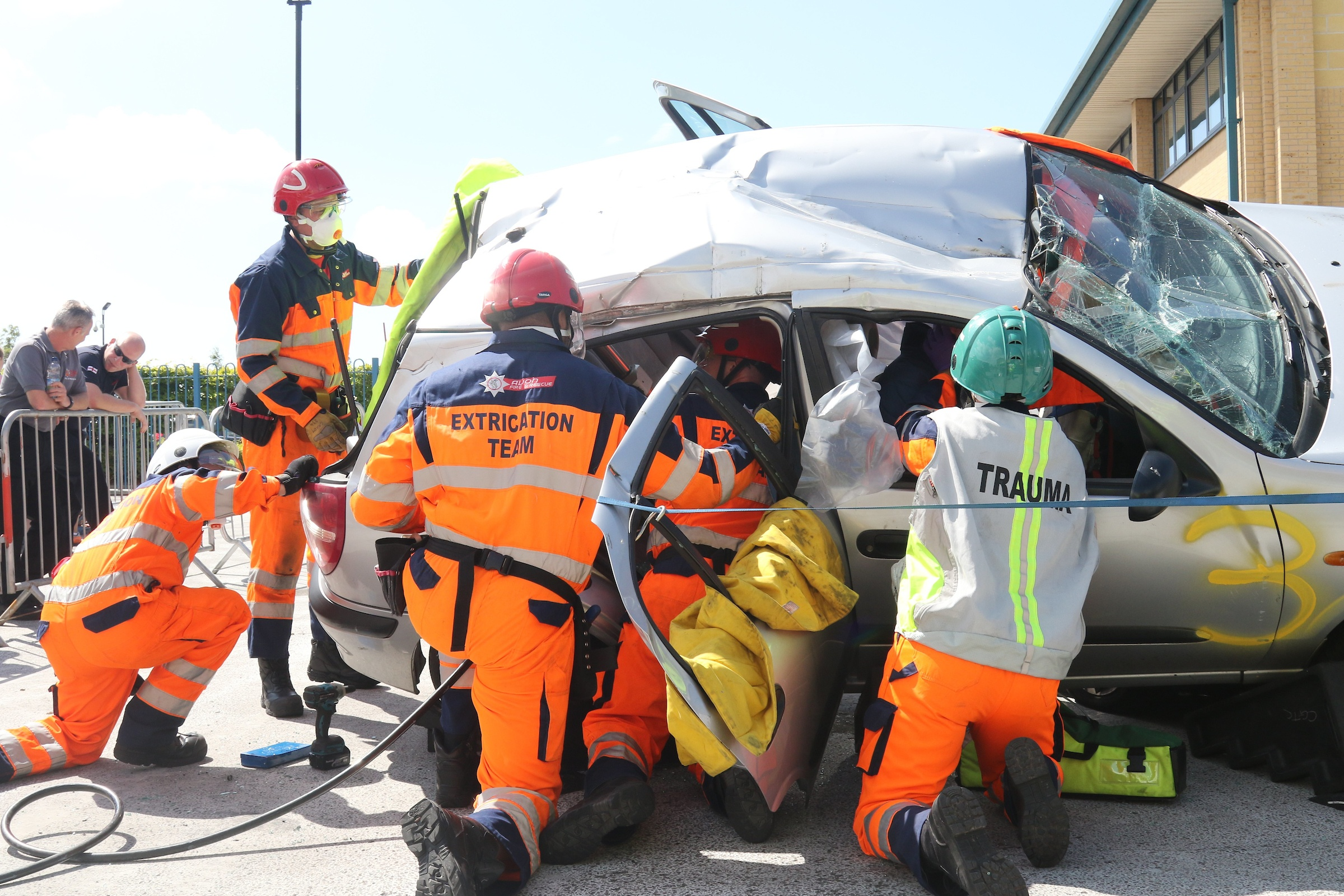 Vehicle on its side with smashed windscreen surrounded by trauma and extrication team wearing full orange high viz and helmets. The teams are working to get people out of the car (this is a simulation as part of the UKRO challenge)