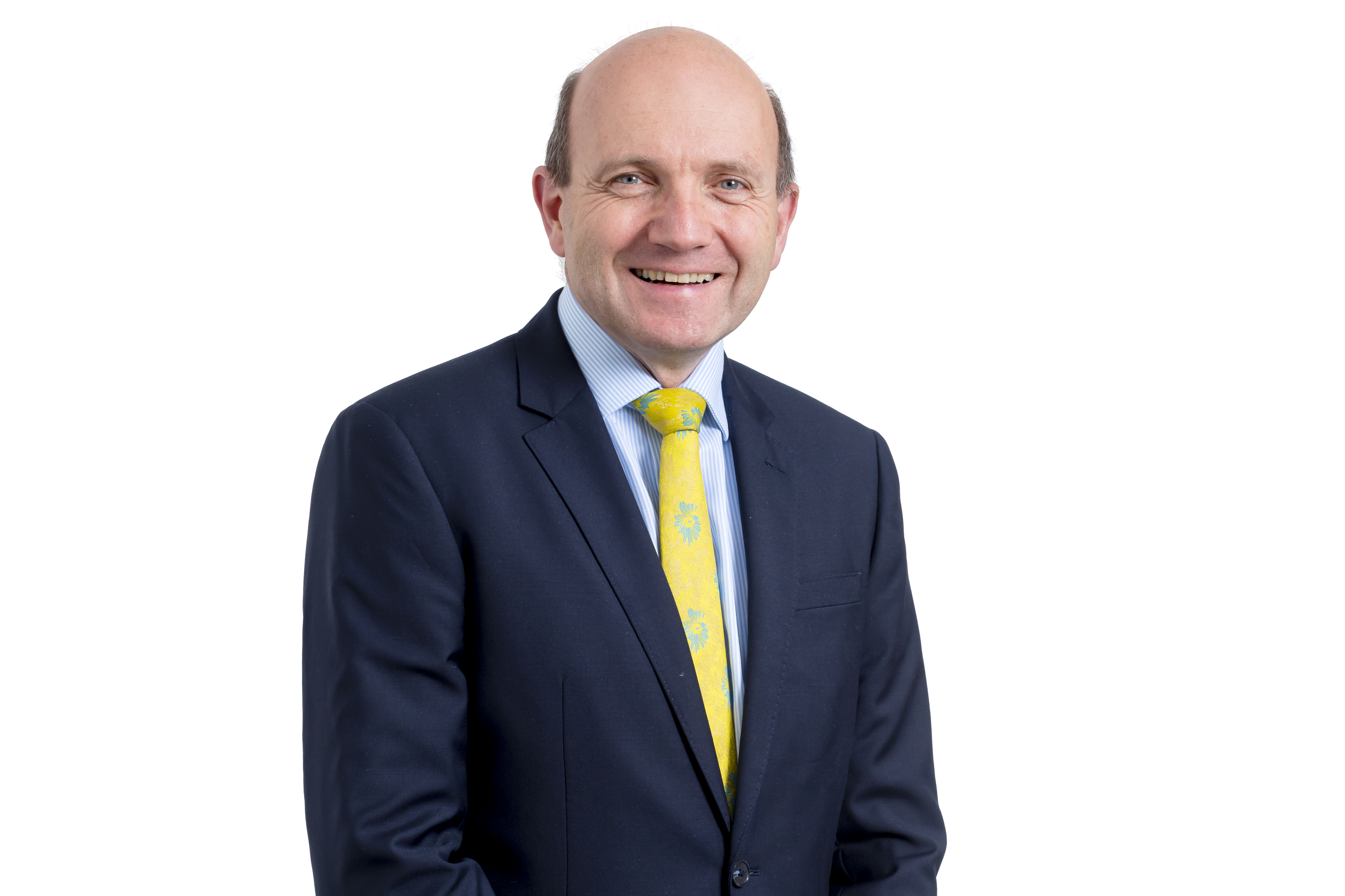 Nick Barwood wearing a navy blue blazer, blue and white striped shirt and yellow floral tie smiles towards camera