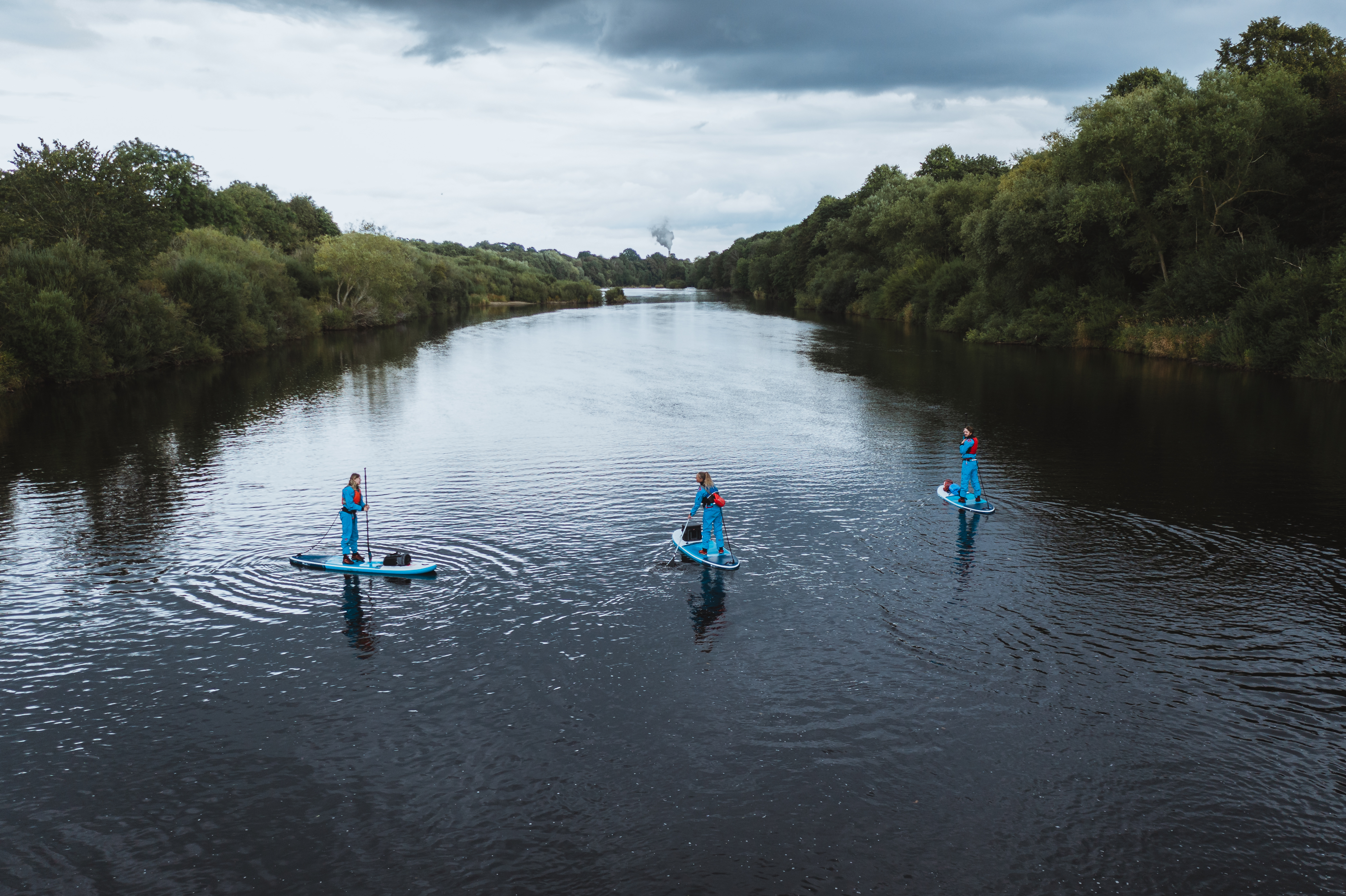Shot of river surrounded by thick green trees, there are three people stood on top of blue paddle boards on the water